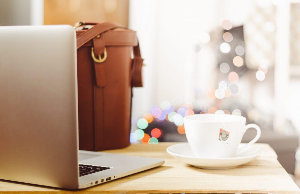 foto van laptop op bureau met kop koffie ernaast