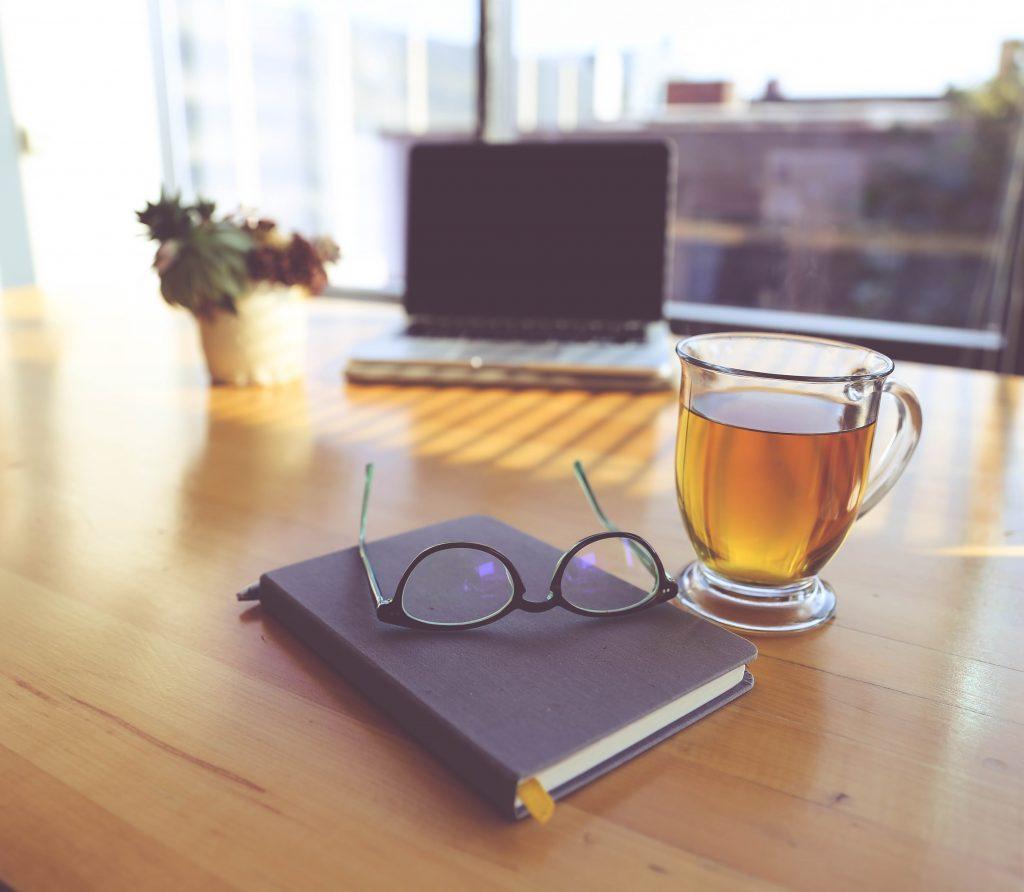 bureau met een agenda, bril en laptop
