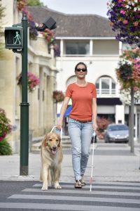 Blinde vrouw steekt de straat over met hulp van een blindengeleidehond