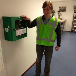 Kees, in BHV-unirorm, staat naast een AED.