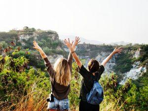 Foto: Twee mensen die met gespreide armen op een berg staan