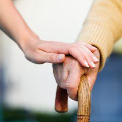 Dokter houdt hand vast van oudere patiënt.