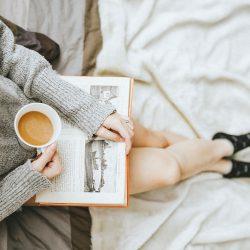 vrouw houdt kop thee vast en leest een boek op een bed.