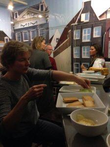 Vrouw maakt toastjes en pratende mensen op achtergrond